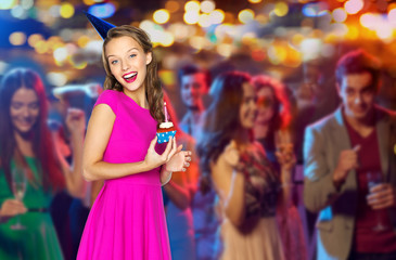 happy woman with birthday cupcake at night club