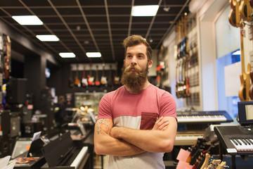 Spoed Foto op Canvas Muziekwinkel assistant or customer with beard at music store