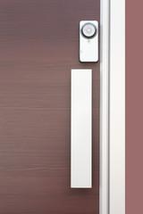 Modern door handle with security system lock on brown wood door