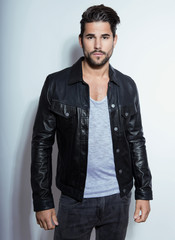 handsome young man posing on grey background with black leather jacket