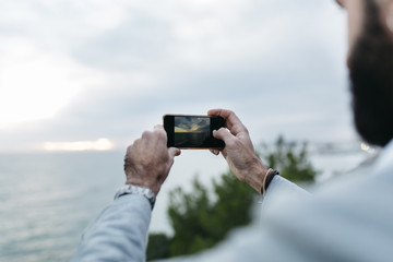 Man holding mobile phone at sunset while taking a photo