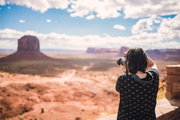 Tourist photographer woman taking pictures photo in Monument Valley, Arizona, USA. Young woman on travel in United States.