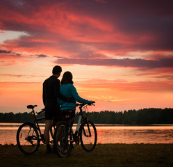 Couple with Bicycles Watching Sunset at River