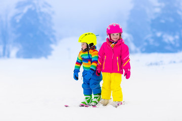 Two children skiing in snowy mountains