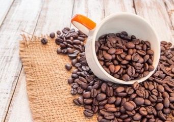 Coffee beans and coffee cup on wooden background