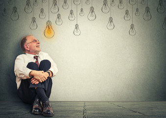 Thinking elderly man in glasses sitting on floor looking up with light idea bulb above head