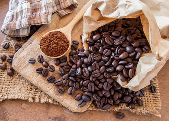Black coffee beans in paper bag on wooden table