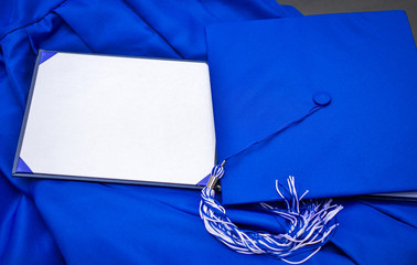Graduation Day. Cap, gown. tassel and blank diploma with copy space for personalized text or message.