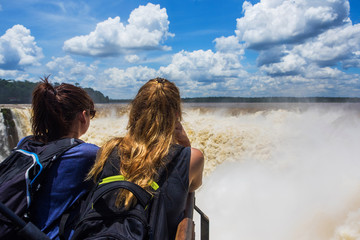 Tourists looking at view at Devil's Throat, the largest cascade at Iguazu Falls, on the border of Argentina and Brazil.