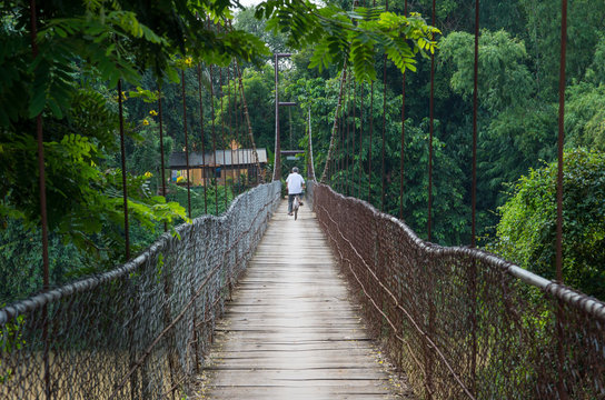 Man riding bicycle to cross bridge in Battambang/Cambodia.