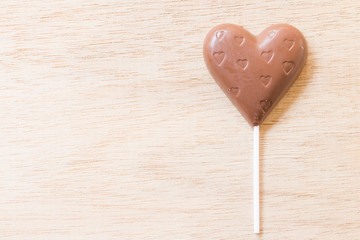 Chocolate hearts candies on wooden background