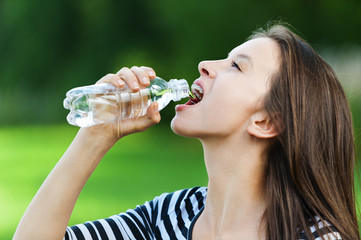 young woman drinks water bottle
