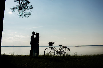 Sillhouette of sweet young couple in love standing. Outdoor shot