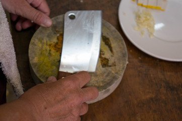 Old hands holding a butcher's knife over a wooden cutting board