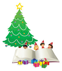 Big book and children by christmas tree
