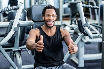Smiling man with thumbs up using exercise machine