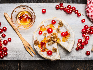 Delicious camembert cheese with berries and sauce on rustic background, top view. Traditional milk dairy product