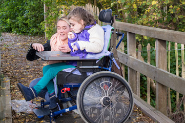 Disability a disabled child relaxing outside / Disability a disabled child in a wheelchair relaxing outside together with a carer