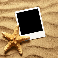 Photo frame on sand background