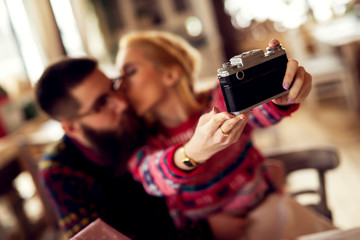 Hipster couple at restaurant making selfie while their are waiting for dinner. Shallow depth of field.