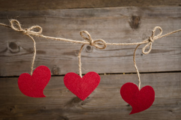 Three Red fabric hearts hanging on the clothesline . On old wood