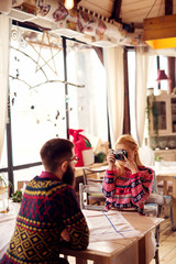 Hipster couple at restaurant waiting for dinner. She is photographing him with old camera. Shallow depth of field.