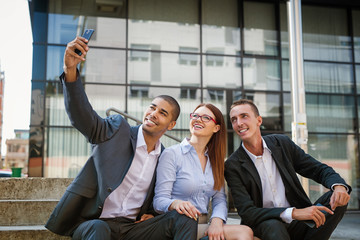 Group of business people sitting at stairs in front of their office and making selife.
