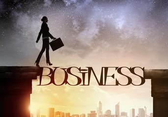 Silhouette of businesswoman over sunrise