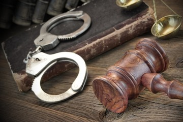 Handcuffs, Judge Gavel And Old Law Books On Wooden Table