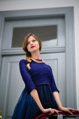 elegant woman in blue dress poses on the stairs