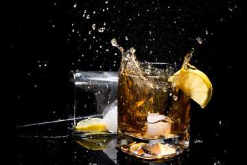 Falling piece of ice in quality glass of whiskey and makes very many splashes and another glass lying on side with lemon slice inside, tubules and ice on black background.