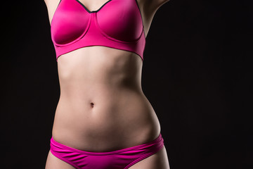 Attractive close up view of young woman wearing sports pink bra and pants with muscular stomach on the black background.