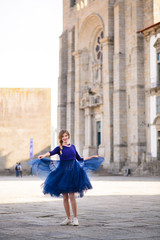 Young elegant woman in blue long flying dress posing at stairway against old city building