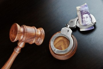 Judges Gavel, Handcuffs And  British Cash  On The Black Table