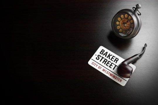Baker Street Sign And Sherlock Holmes Symbol On Black Table