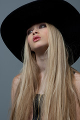 Blond woman with long beautiful hair and smoky eyes in a hat. St