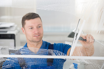 Worker Cleaning Soap Sud On Window With Squeegee