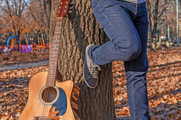 Man and guitar leaning on a tree in autumn park