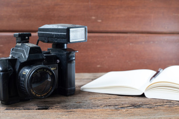 Vintage camera and book on wooden background