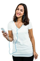 Portrait of woman listening music while using mobile phone