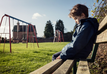 Lonely child with depression sitting on play park playground bench