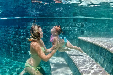 Happy family - mother hold in hands baby girl and dive down with fun in beach pool, active parents lifestyle, people water sport activity and underwater swimming lesson on summer vacation with child.