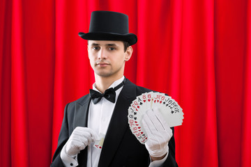 Wall Mural - Magician Holding Fanned Out Cards Against Red Curtain