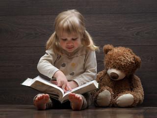 Маленькая девочка читает большую книгу. Рядом сидит игрушка, медвежонок. Девочка блондинка с двумя хвостиками, в джинсах. Ребенок учится читать и водит пальчиком по строкам текста. Девочка босиком