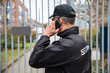 Security Guard Talking On Mobile Phone In Front Of Gate