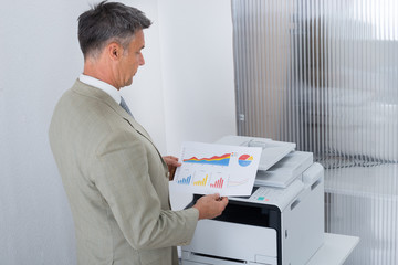 Businessman Looking At Paper With Graphs By Color Printer