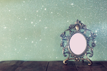 low key image of antique blank victorian style frame on wooden table. retro filtered image with glitter overlay. template, ready to put photography
