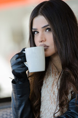 Woman with a unique fleshy lips wearing leather jacket and gloves holding a coffee cup, sitting in cafeteria