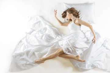 Expressive woman sleeping. Full length high angle view of a young woman sleeping on white background. Dreaming of becoming ballet dancer