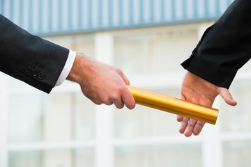 Businessman Passing Relay Baton To Colleague Wall mural